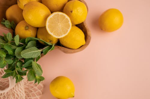 Fresh lemons and mint sprigs above zero waste bag