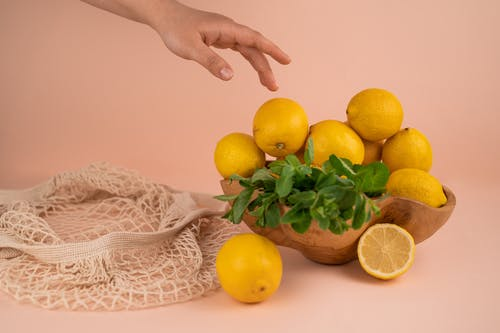 Crop person against fresh lemons and mint sprigs in bowl
