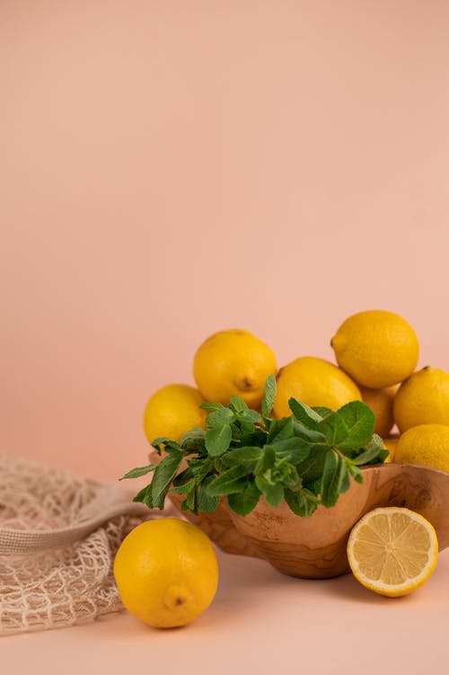Ripe whole and cut lemons with mint foliage in wooden bowl near zero waste bag on pastel background