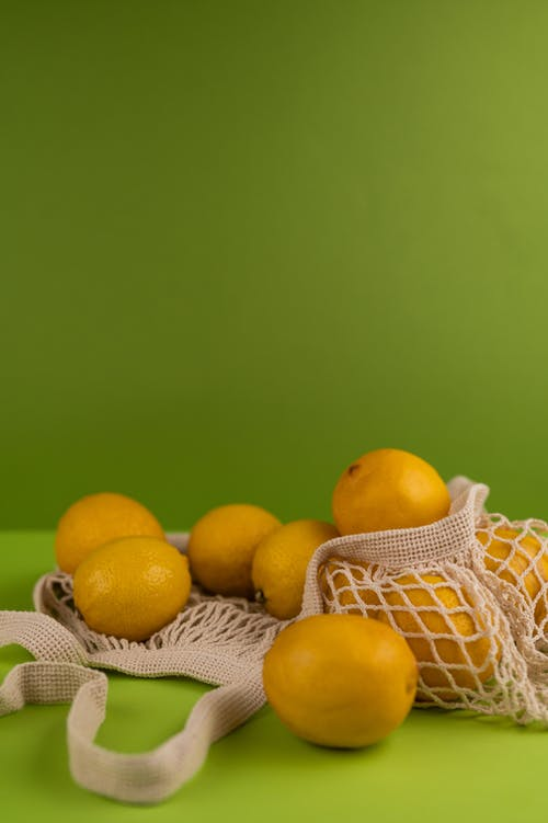 Whole ripe lemons with pleasant scent in waste reduce bag on smooth green surface