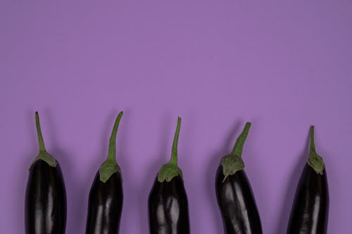 Top view of raw aubergines with smooth peel and stalks on calyces on violet background