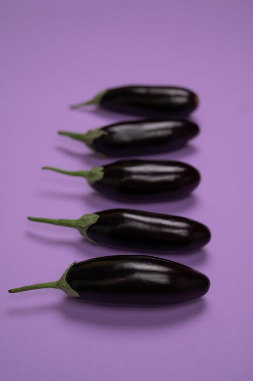 Fresh eggplants with stems on violet background