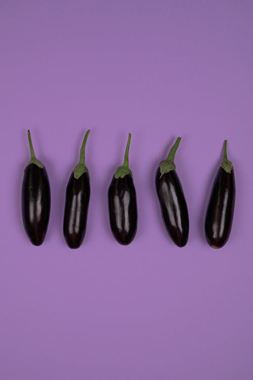 Overhead view of fresh aubergines with smooth peel and stems on calyces on purple background