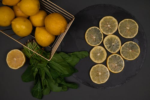 Top view of fresh whole and cut lemons on black chopping board near spinach foliage on dark background