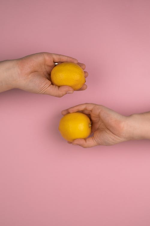 Crop unrecognizable person with ripe whole yellow lemons demonstrated on monochrome pink background