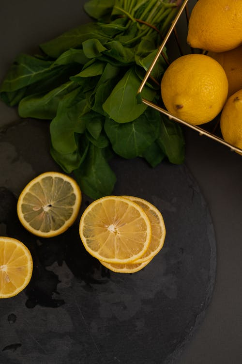 Top view of fresh juicy lemons in container and slices on plate near leaves on dark table