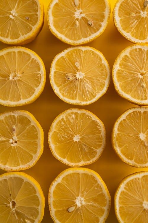Closeup of sliced lemons on yellow surface
