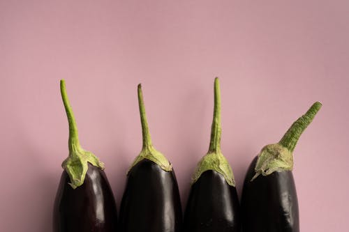 Top view of ripe dark eggplants with green stem placed in row on lilac background