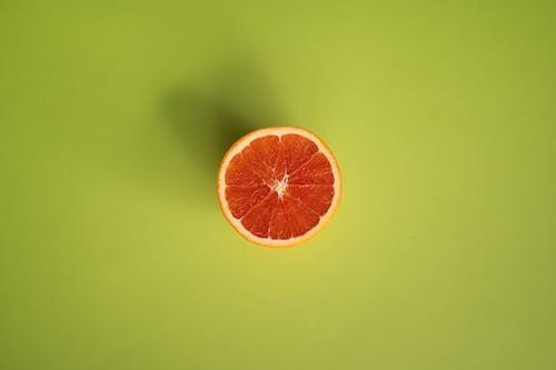 Slice of grapefruit on green surface