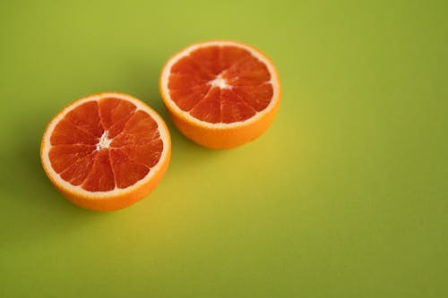 Tasty ripe citrus fruit with juicy pulp cut in half placed together on bright green surface