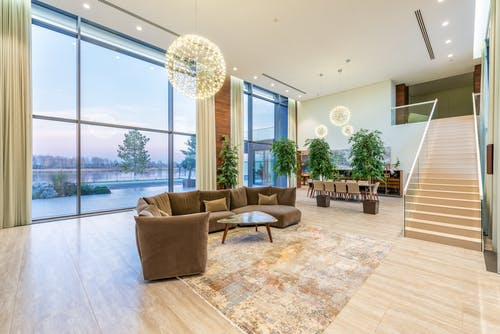 Spacious lobby with sofa near stairs and glass transparent wall