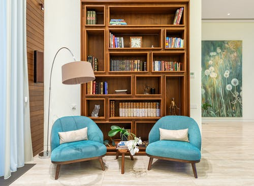 Living room with cozy chairs near lamp and wooden bookcase