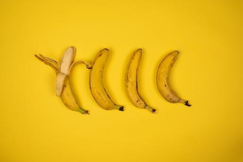 Tasty fresh bananas with peel on yellow background