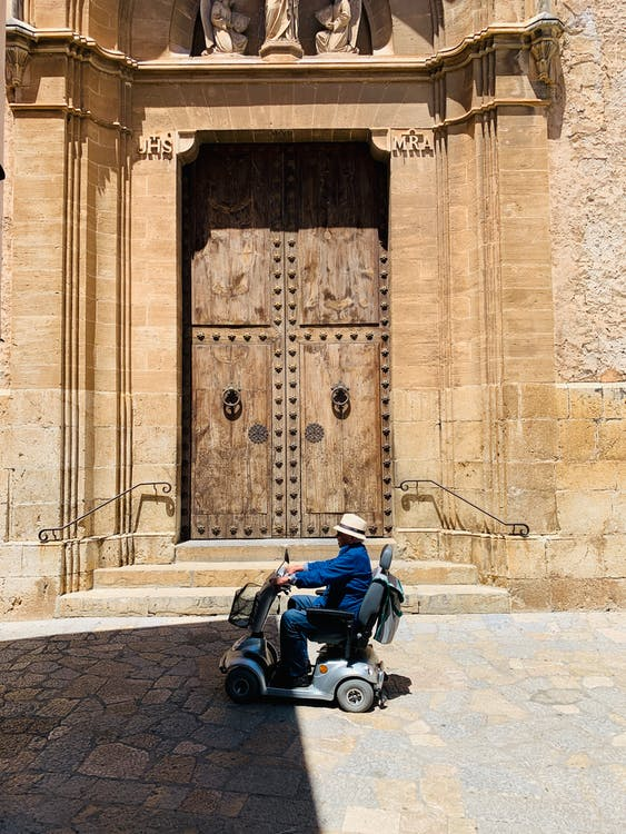 Man on Mobility Scooter Passing by a Wooden Door