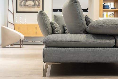 Part of spacious modern living room interior with comfortable gray couch and pillows in selected focus
