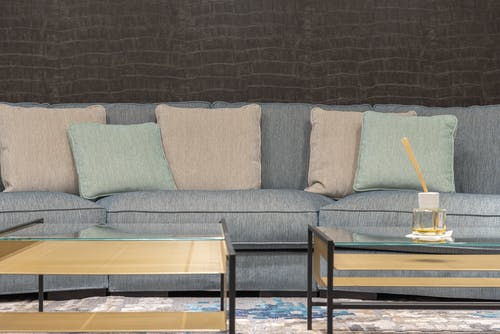Comfortable gray sofa with soft cushions near coffee tables with glass tabletops in modern living room