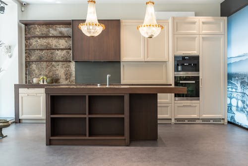 Interior of spacious classic styled kitchen with white and brown wooden furniture and crystal chandeliers