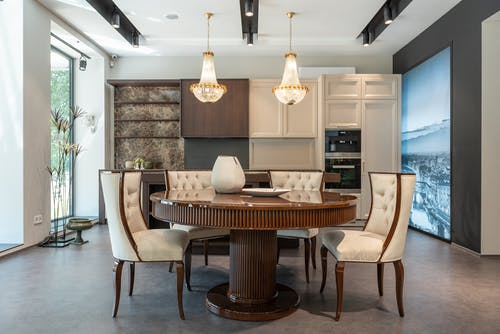 Interior of elegant spacious kitchen with wooden furniture and shiny crystal chandelier hanging over dining zone with round table and comfortable chairs