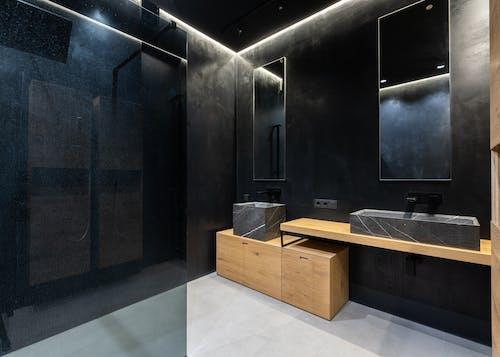 Creative minimalist bathroom with black walls and sinks
