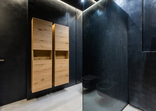 Wooden cupboards hanging on black wall near toilet bowl and shower cabin in contemporary bathroom
