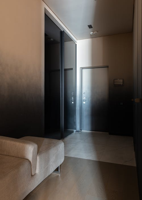 Comfortable couch and big wardrobe with glass mirrored doors in spacious corridor of modern apartment