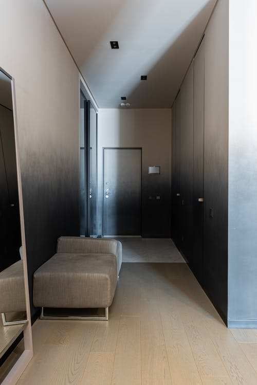 Corridor with couch and mirror in contemporary apartment
