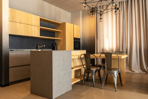 Table with chairs placed in spacious kitchen with wooden cabinets and appliances in stylish apartment with curtains on window at home