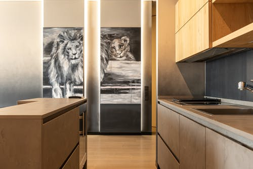 Counter placed in kitchen with wooden cupboards and sink against wall with creative picture of lion in light modern apartment