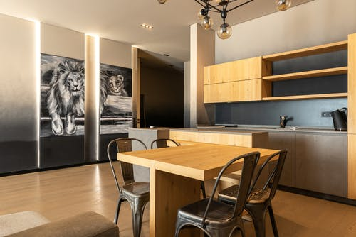 Wooden table with chairs placed in kitchen with cupboards and shelves in stylish spacious apartment with picture of lion at home