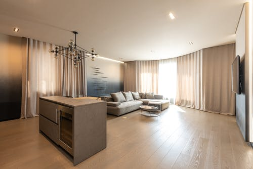 Interior of modern apartment with counter placed near comfortable sofa at decorated wall and window with curtains at home with TV