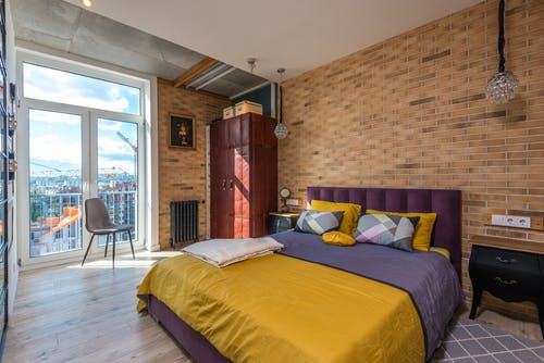 Purple and Yellow Bed Beside a Brown Brick Wall