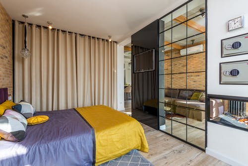 Comfortable bed with colorful bedclothes and pillows placed against wall with TV and fireplace in modern bedroom with curtains at home