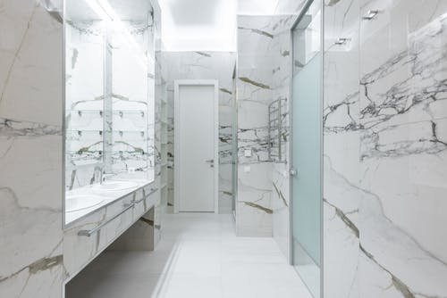 White sinks with taps placed on cabinet at wall in light contemporary bathroom with doors and bright illumination at home
