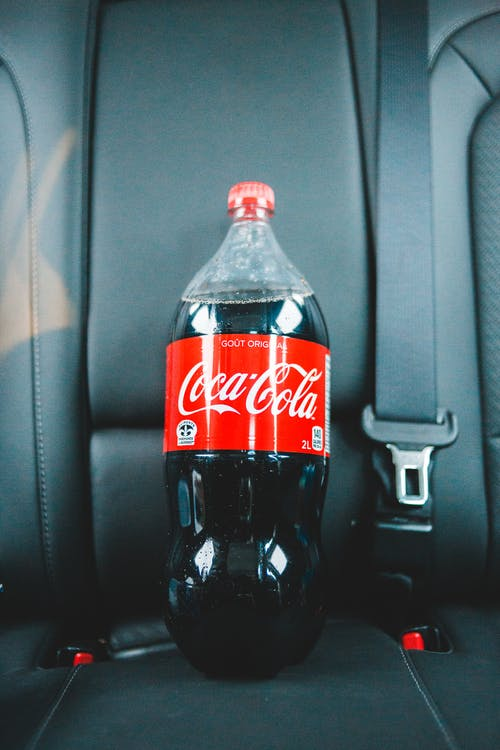 Cola in plastic bottle on car seat