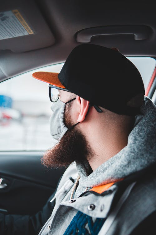 Side view of bearded male in glasses wearing cap and mask while sitting in car and looking away