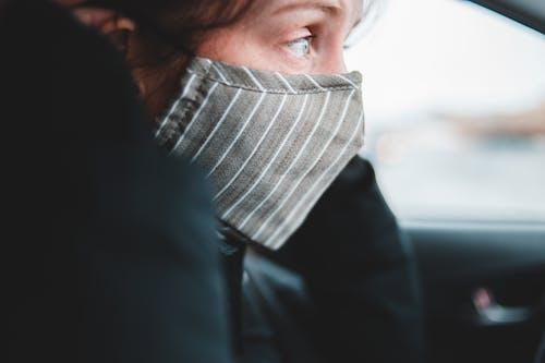 Woman in mask sitting in car
