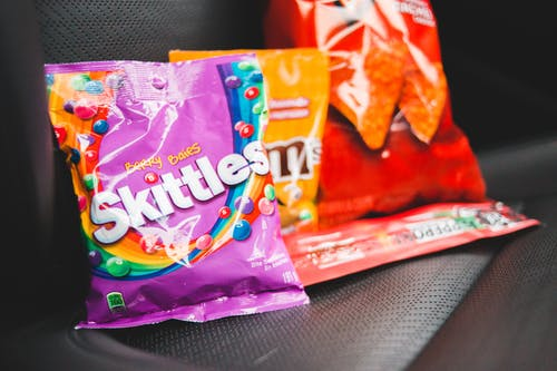 Closeup composition of multicolored packages with tasty treats placed in row on dark seat of car
