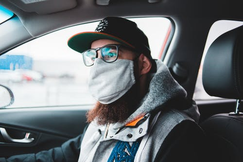 Young bearded hipster in glasses and protective mask wearing warm clothes and cap while sitting in car and looking away