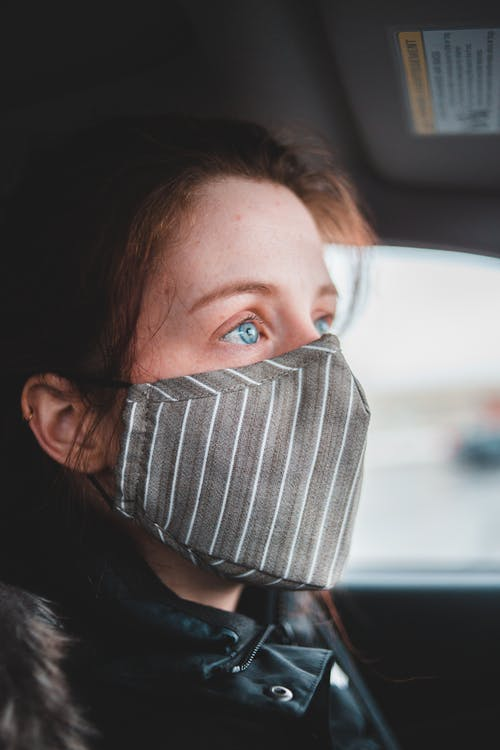 Attractive woman in mask sitting in car