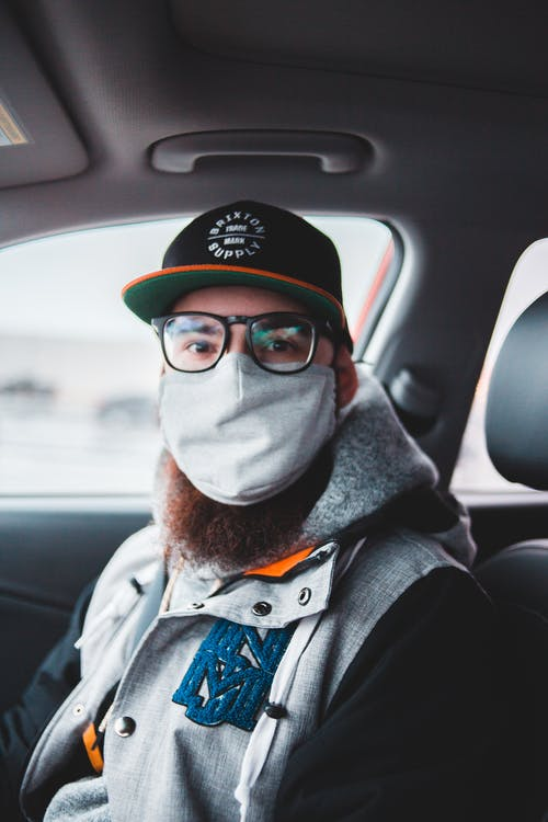 Young bearded hipster with glasses and mask wearing warm jacket and hat while sitting in modern automobile and looking at camera