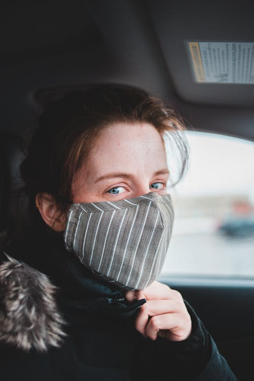 Calm female in warm clothes wearing protective mask while sitting in modern automobile and looking at camera