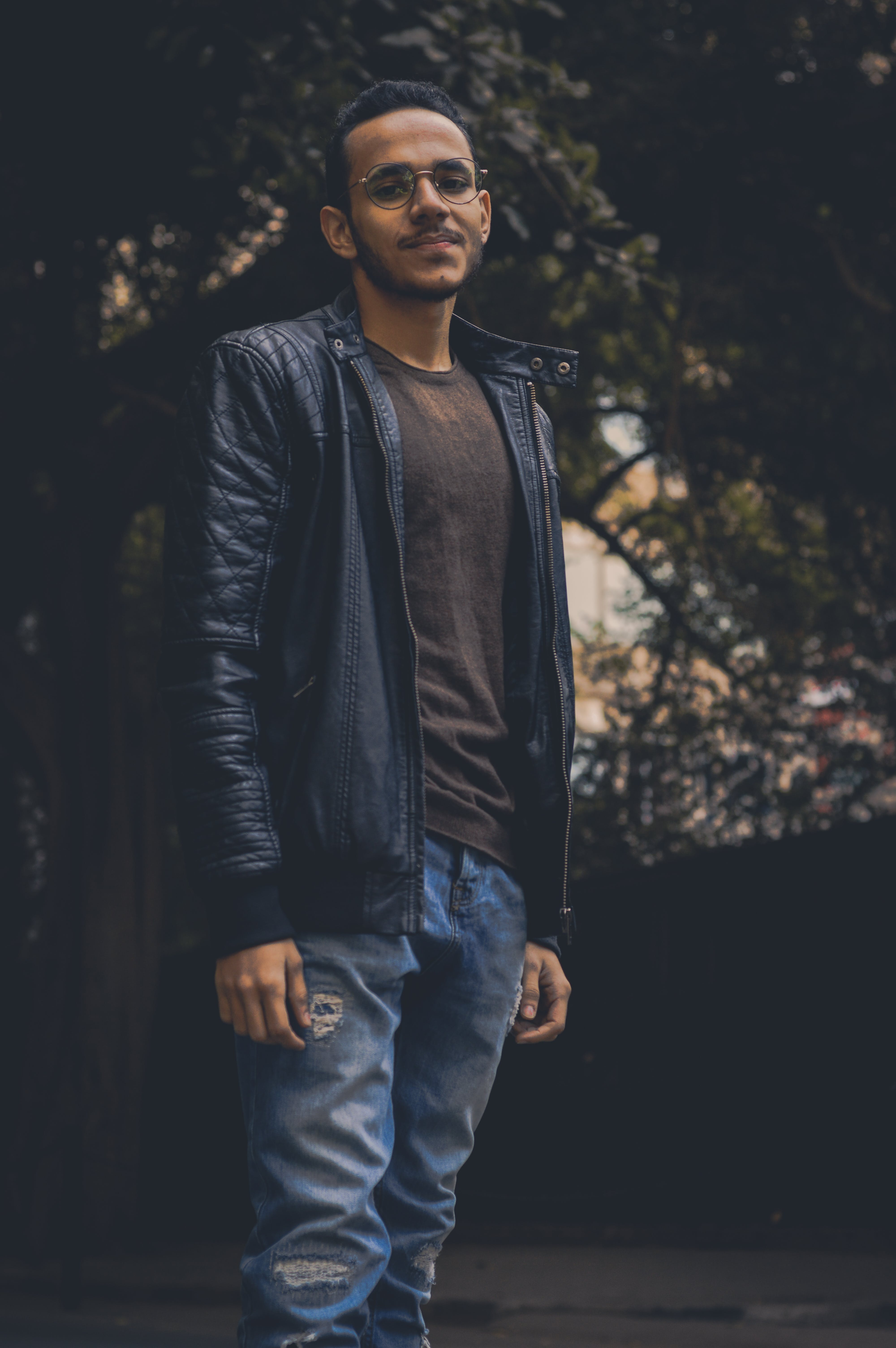 Man in Brown Shirt and Black Leather Zip-up Jacket and Blue Denim Pants