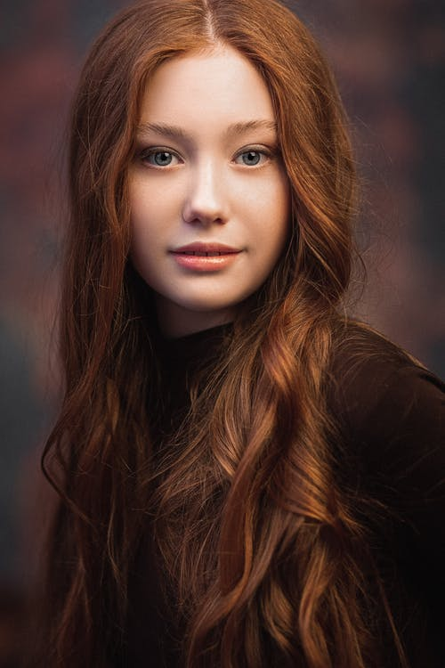 Calm woman with long wavy red hair