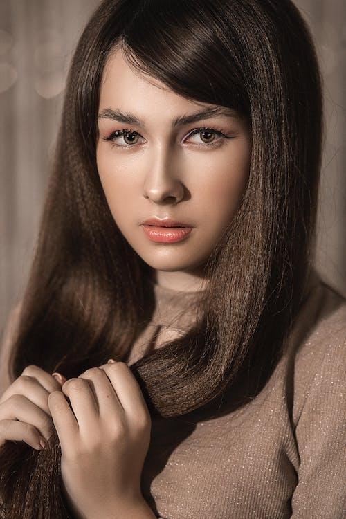Crop gentle female in beige sweater looking at camera on brown blurred background of studio