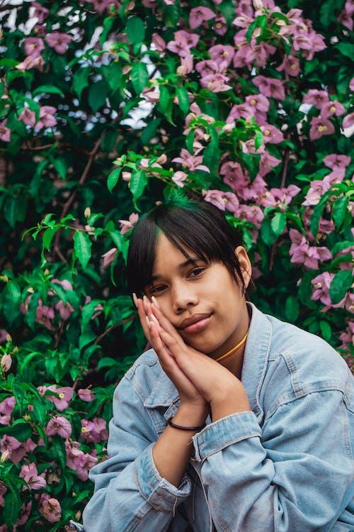 Woman in Blue Denim Jacket Sitting on Pink Flower Field