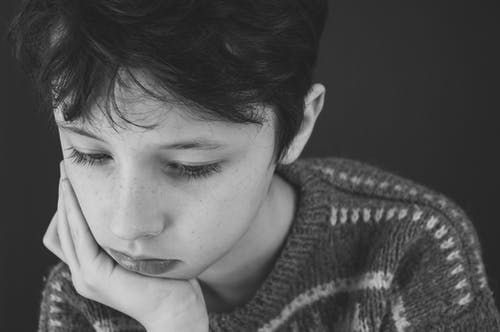 Black and white of sad boy with short dark hair in casual clothes covering face with hand while looking down