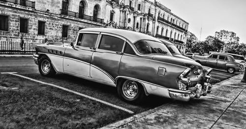 Greyscale Photo of Vintage Car Parked Beside Building