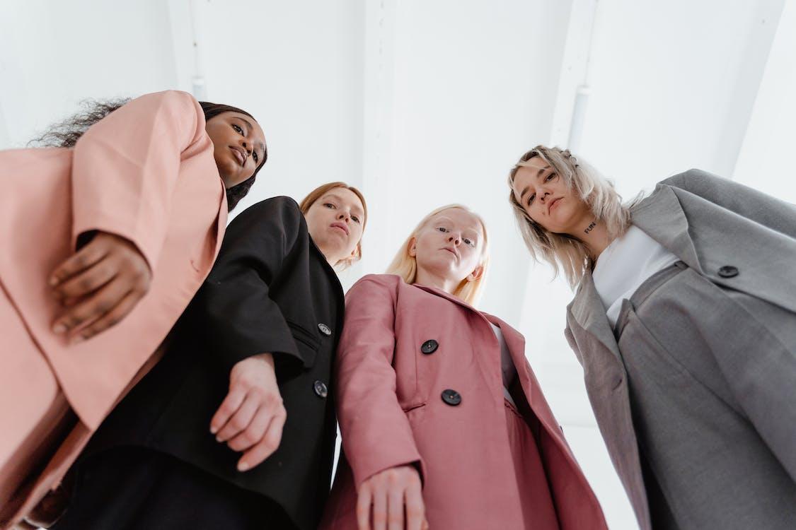 3 Women in Black and Pink Coat Standing Beside Woman in Brown Coat