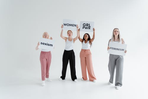 Women in White Tank Top and Pants Holding White Cardboard with Text