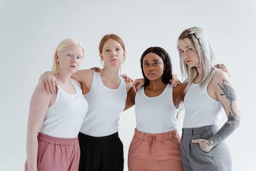 Women in White Tank Top Standing Side by Side